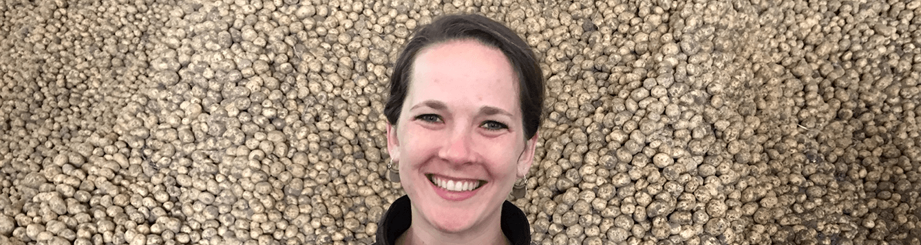 CALS alumna Kendra Levine in front of a background of harvested potatoes