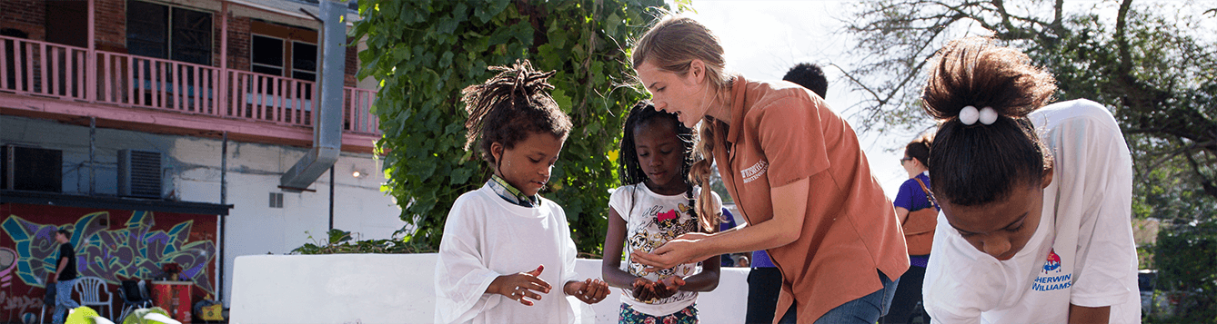 UF/IFAS Extension agent helps two girls plant seeds in a garden