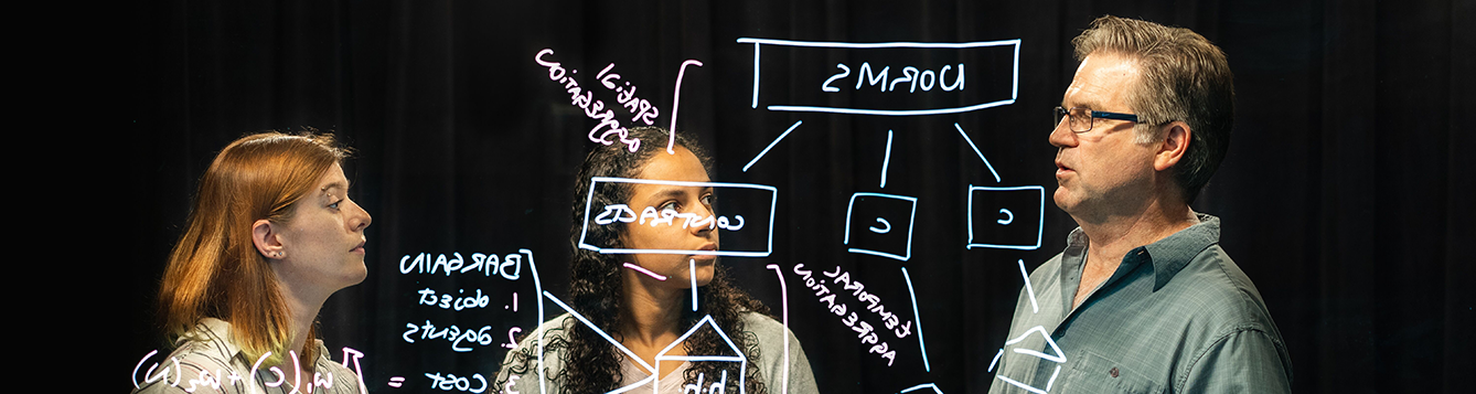agricultural and biological engineering faculty member teaches two students science problems on a light board.