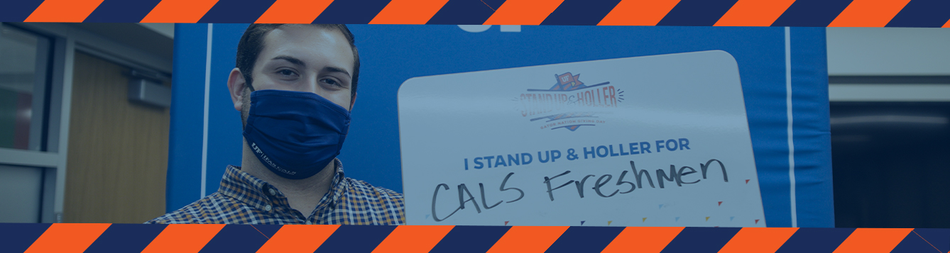 "A student holding a sign that says ""I stand up and holler for CALS Freshmen"""