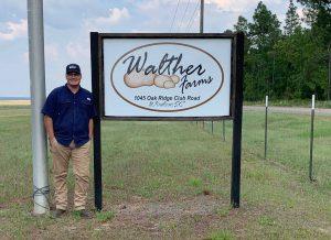 "Photo of Paul Hawkins next to sign reading ""Walther Farms 1045 Oak Ridge Club Road Windsor South Carolina"""