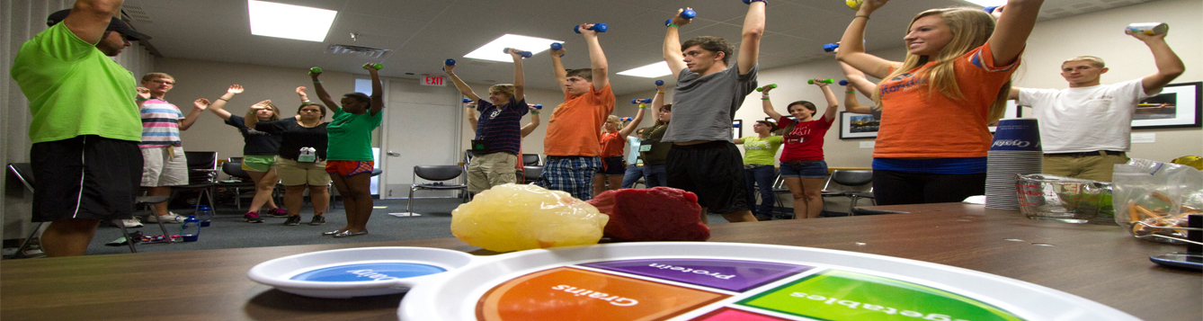Young people lifting weights for physical activity with USDA MyPlate, pound of fat model, and pound of muscle model in foreground