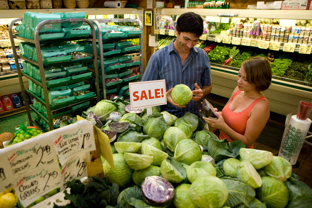 Two customers buying produce in a grocery store.