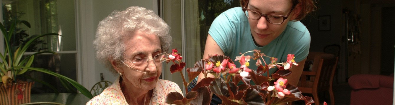 senior woman with younger woman caring for house plant