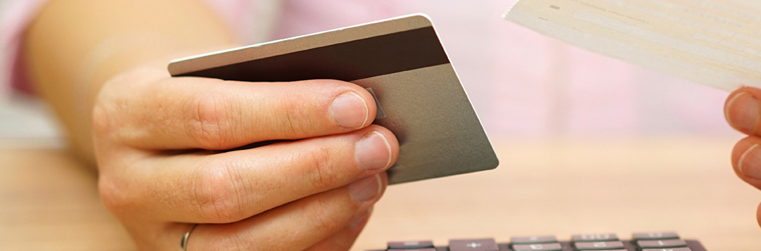 Woman holding credit card and bill