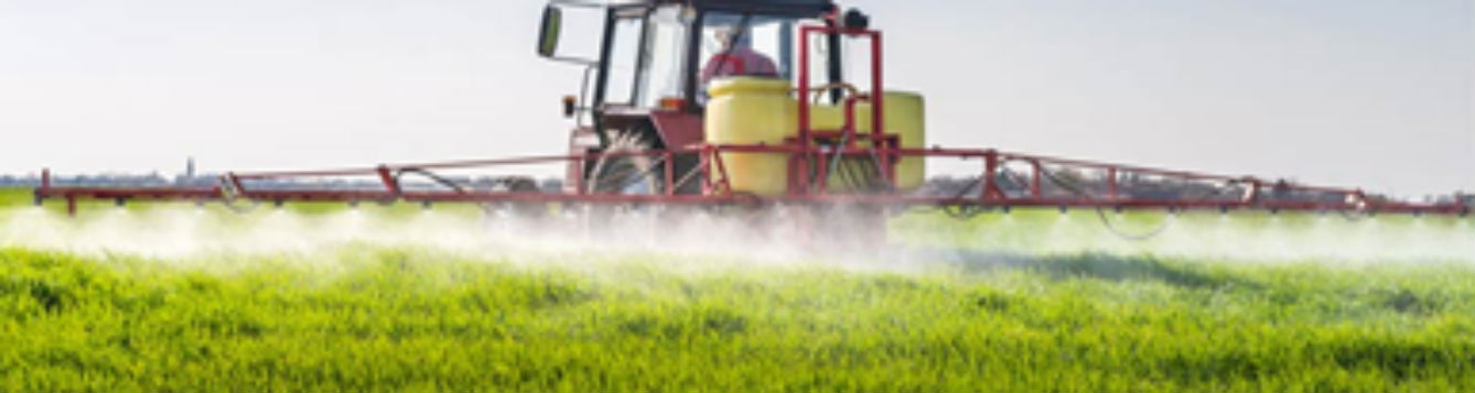liquid spray eminating from boom over agriculture crops