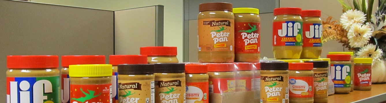A line of peanut butter jars along countertop