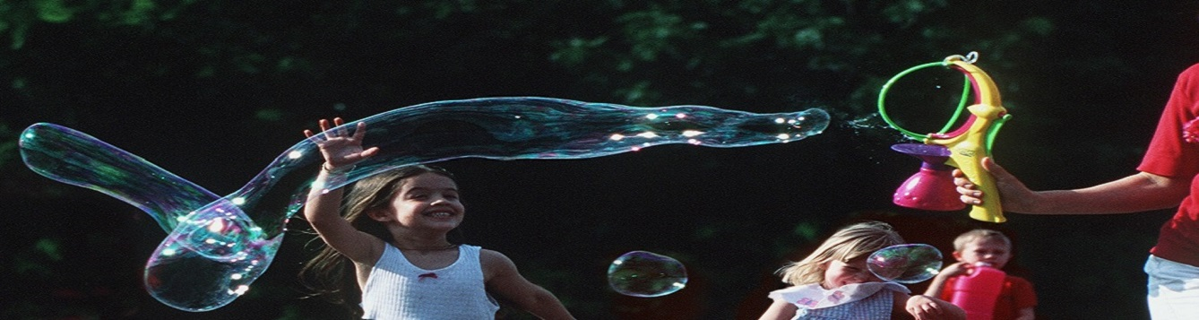 Children playing with large bubbles in a field