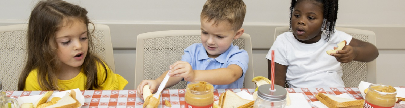 children eating peanut butter and snacks at a table,