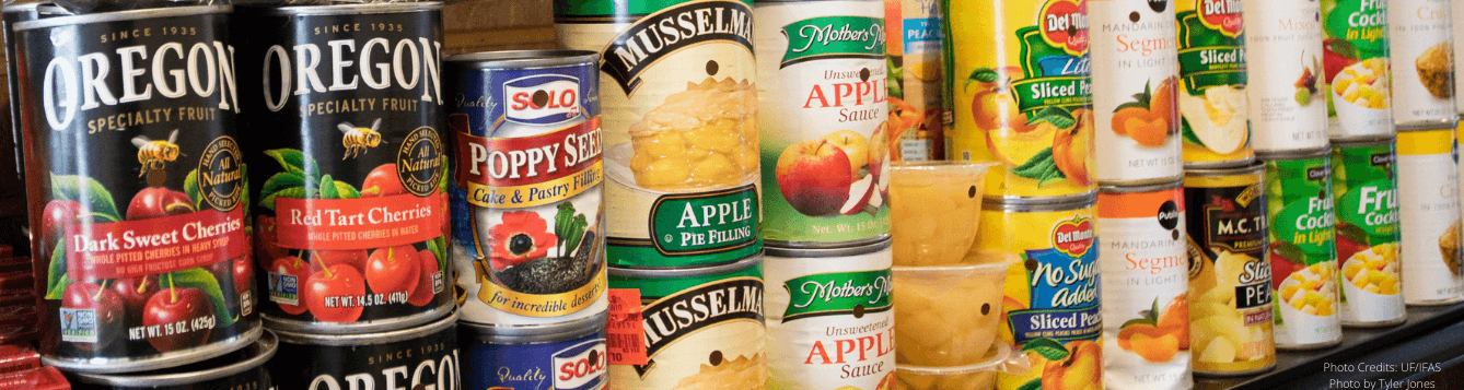 Stacked canned foods on a shelf.