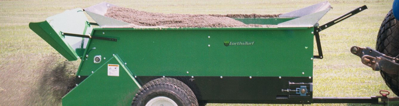 A mechanical topdresser has a hopper full of screened compost product ready to apply to turfgrass.