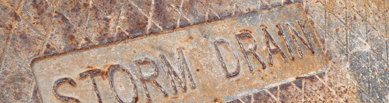 Rusted letters spell STORM DRAIN