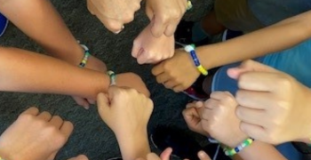 Many people with their hands together in circle