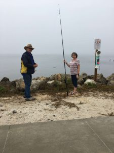 Two people fishing near a bird rescue sign.