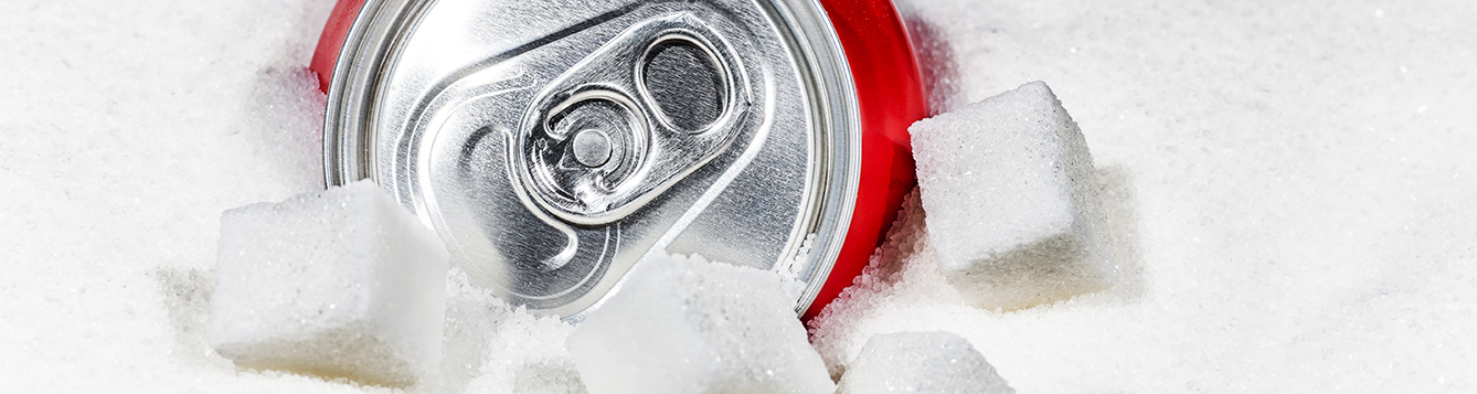 Can of soda surrounded by sugar and several sugar cubes