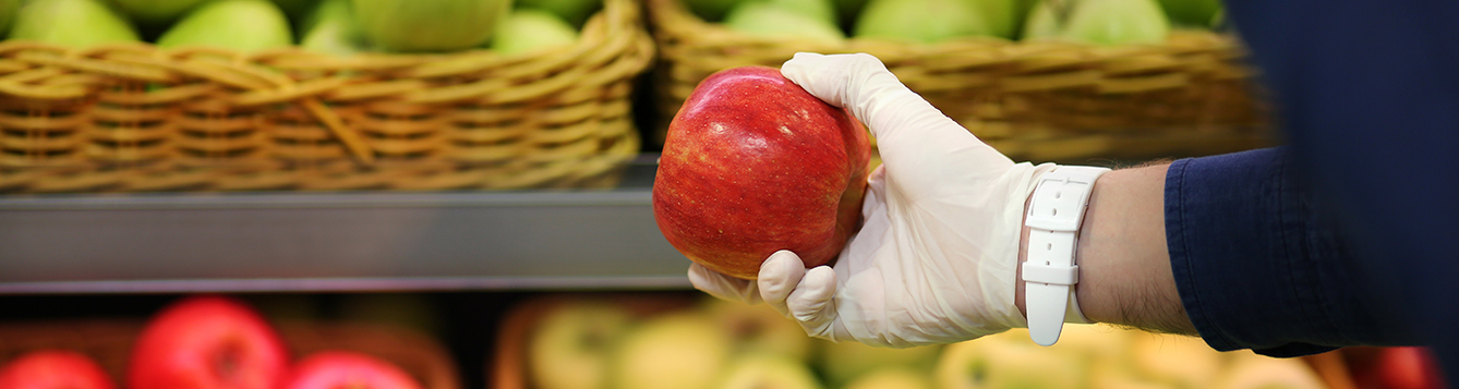 Gloved hand holding an apple in a grocery store