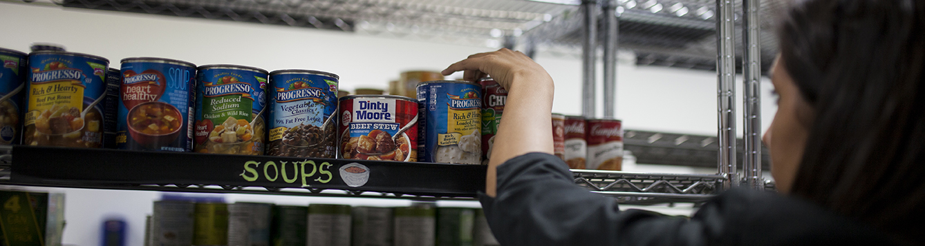 a volunteer reaches to stock cans of soup on a shelf at a food pantry