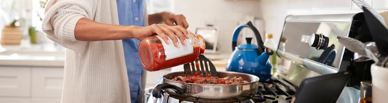 Woman pouring tomato sauce into a pan