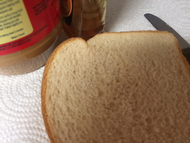 bread slice with peanut butter jar