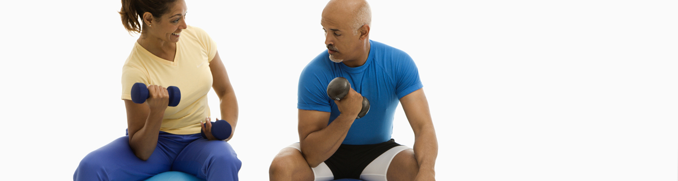 Mid adult multiethnic man and woman balancing on blue exercise balls while working out with dumbbells.