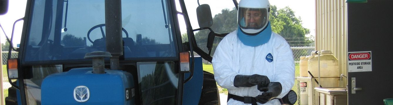 Properly suited pesticide applicator beside tractor sprayer ready to apply a chemical with danger signal word.