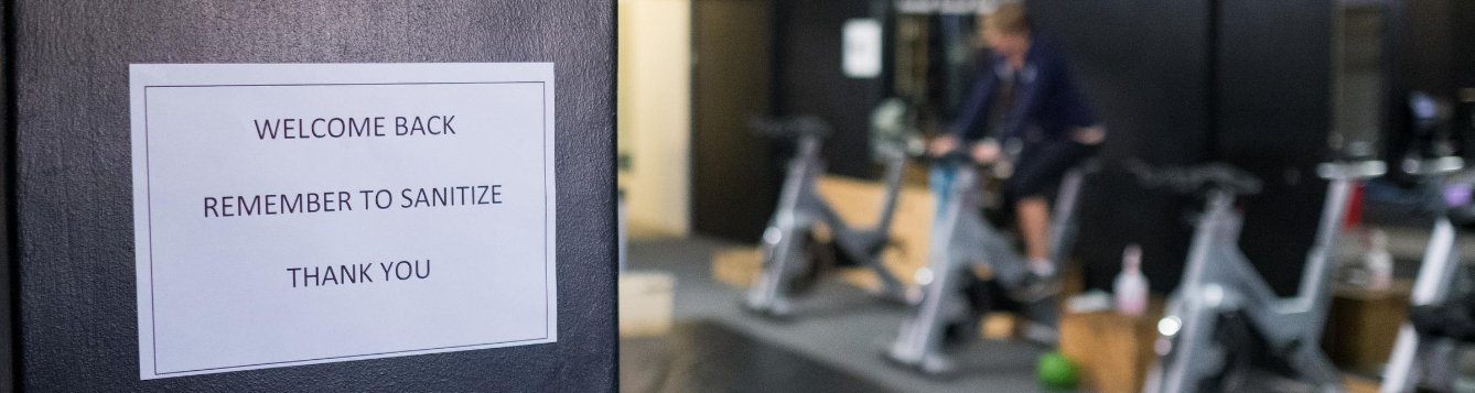 person working out in gym with cdc guidelines sign