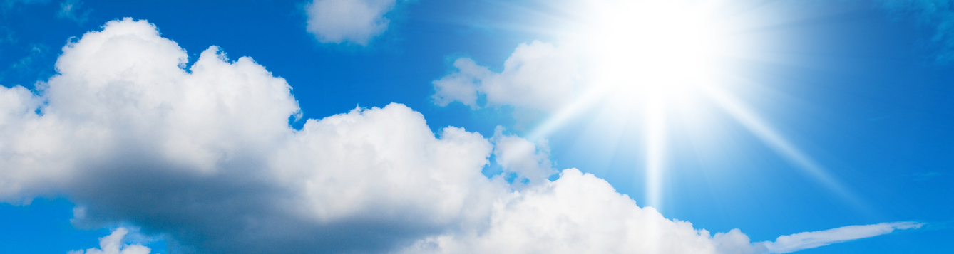 summer sun in the blue sky with white puffy clouds