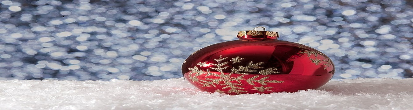 A red Christmas ornament laying in the snow while snow is falling