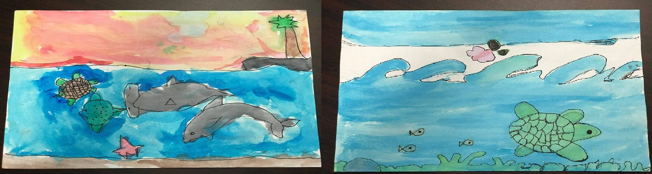 Two children drawings, one of dolphins and an island with a palm tree. The other is of a sea turtle and fish.