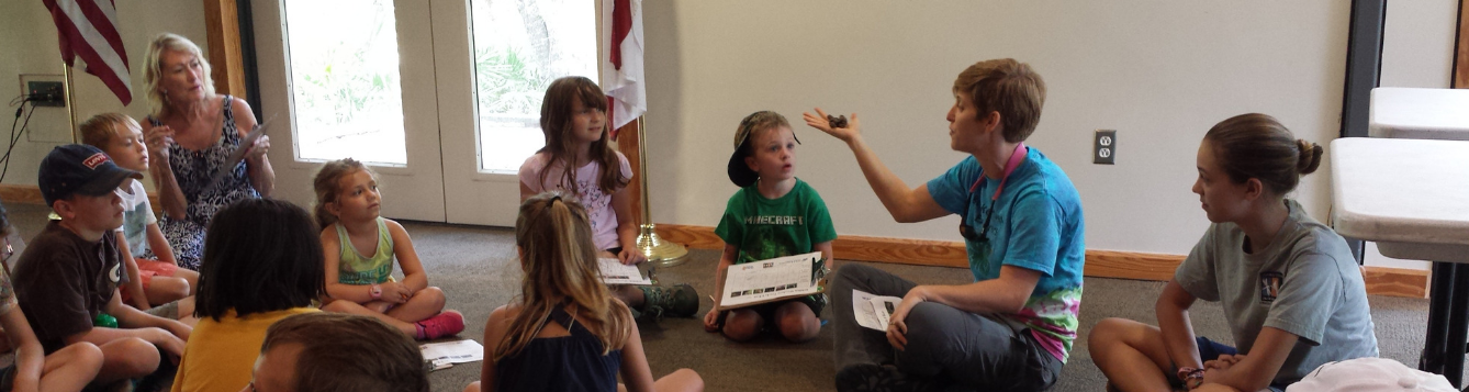 Lara Milligan, Natural Resources Agent holding up replica scat as part of a youth program at Brooker Creek Preserve Environmental Education Center.