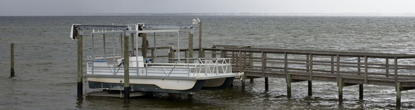 a pontoon boat on a boat lift, with a threatening storm in the distance.