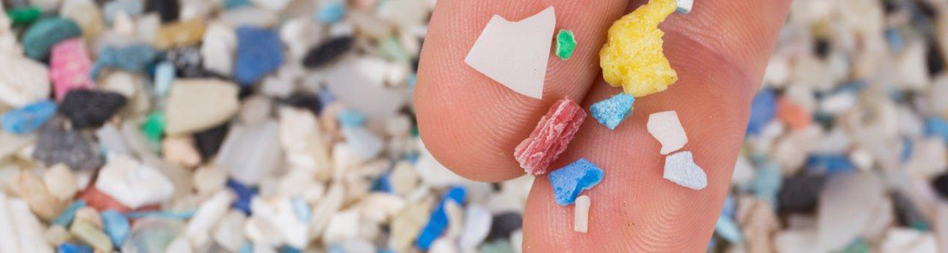 Close-up photo of microplastic pieces with two fingers for scale.