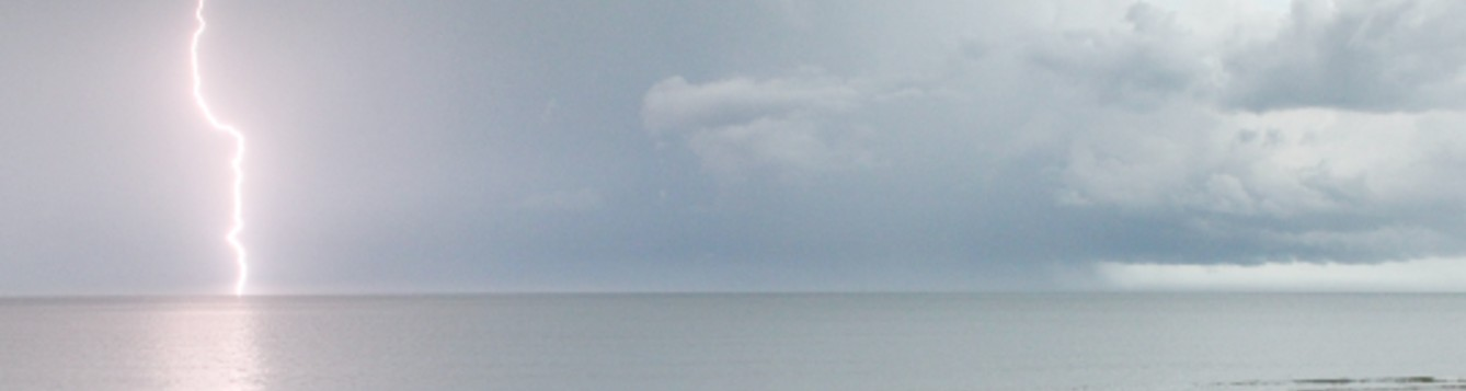 View of sky with storm clouds and a lightning strike over water.