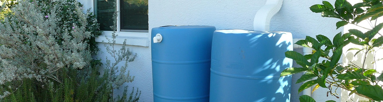 working rain barrels stationed beside house