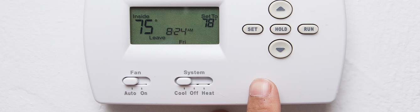 A wall home thermostat being adjusted