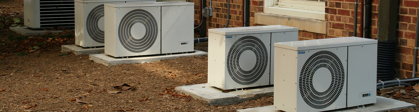 air conditioning units line a row of homes