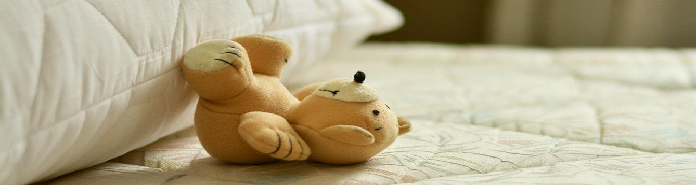 teddy bear on a sheetless matress