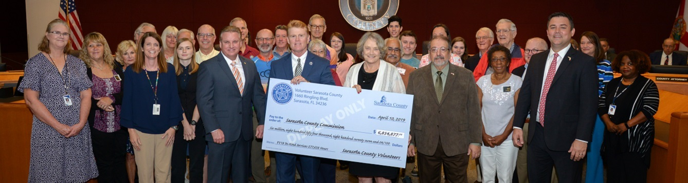 County commissioners recieve mock check for volunteer contributions for 2017-18