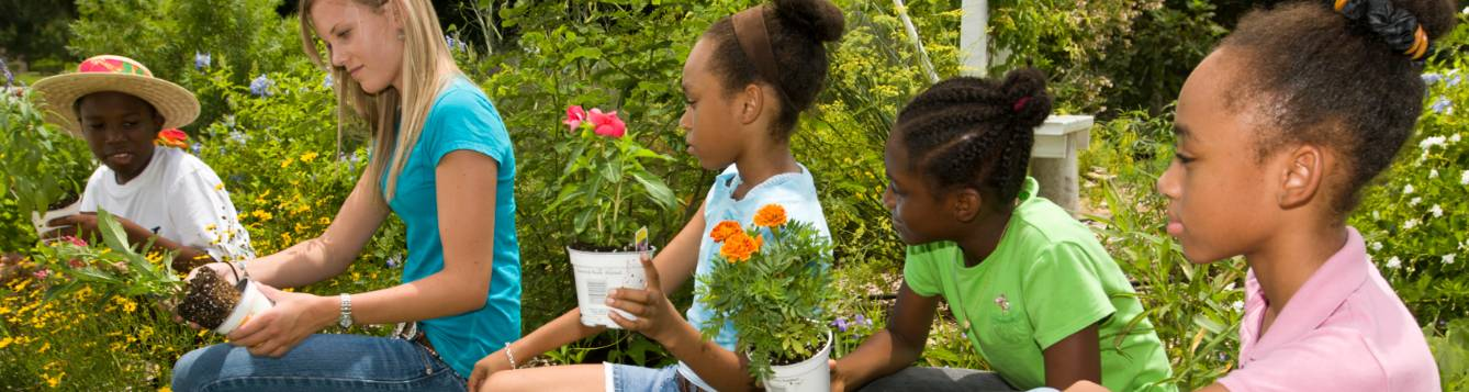 Children learning to garden from an adult