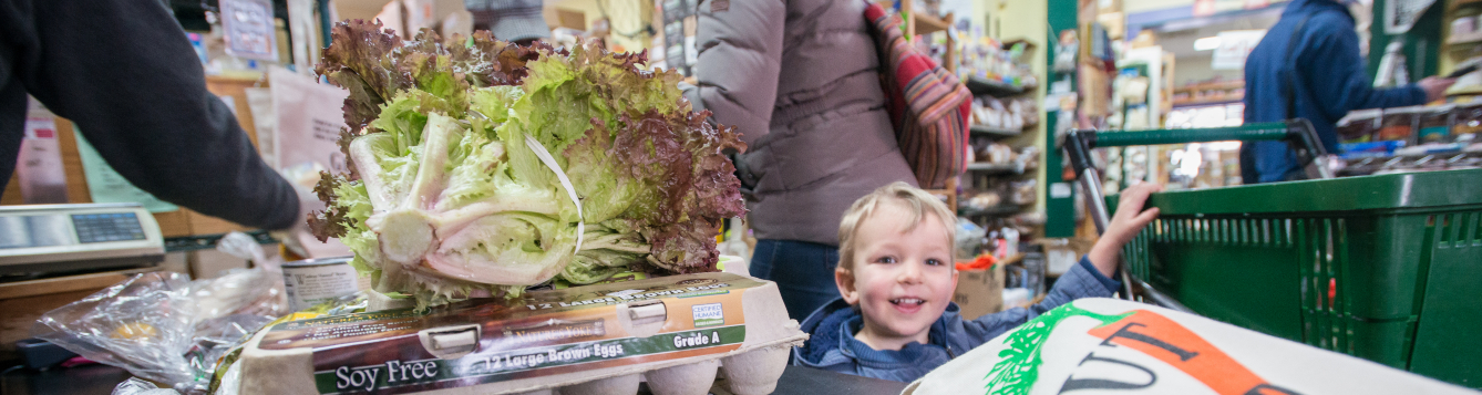 a child smiles at the checkout line in a food store