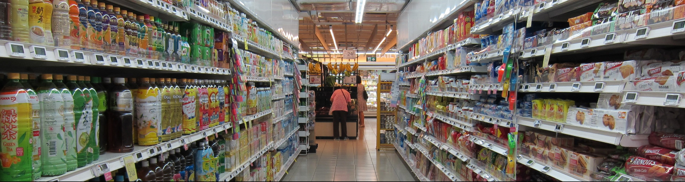a single shopper stands at the end of an otherwise vacant grocery aisle