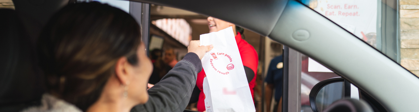 a woman driver picks up a fast-food order at a restaurant's drive-through window