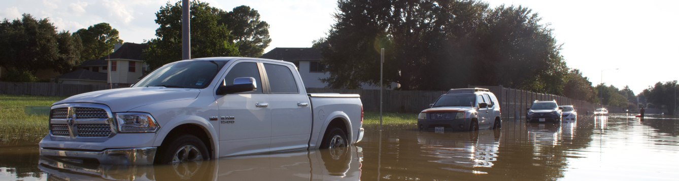 a row of vehicles sit in standing water on a flooded neighborhood road