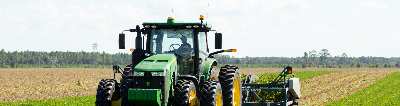 A tractor turns crops in a Florida field. [CREDIT: UF/IFAS]