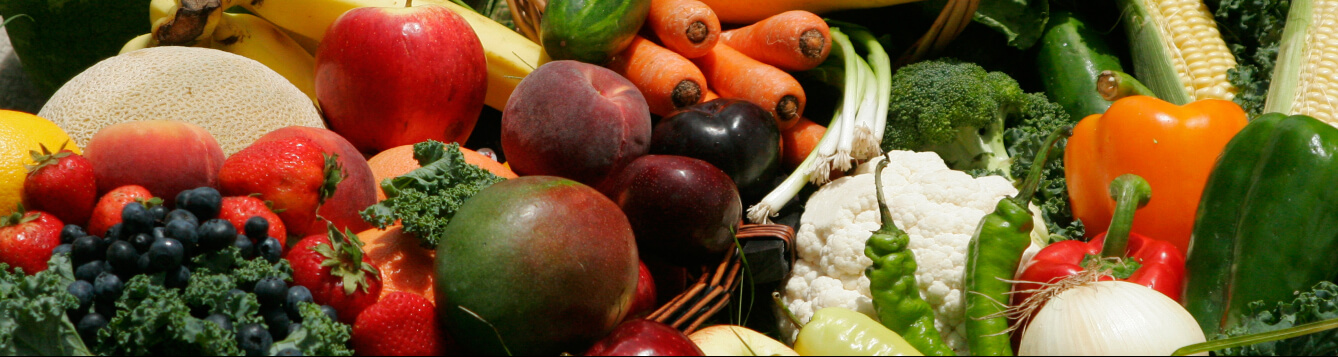 various fruits and vegetables arranged for photographic display, including apples, carrots, bananas, peppers, mangos and more