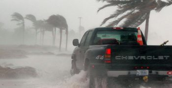 a government pickup drives along a rapidly flooding coast during a storm