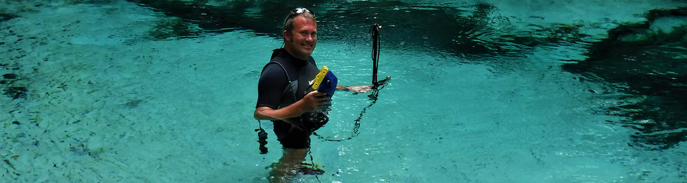 Man in wetsuit standing in Florida spring pool with measurement equipment