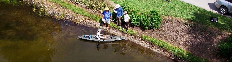 women in kayak on stormwater pond talking to people onshore