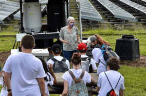 University professor discusses composting with group of students.
