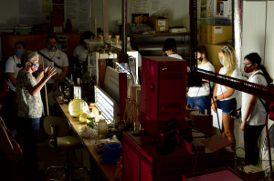University professor talking to students in red light lab.